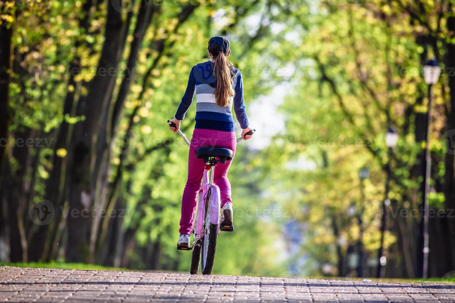 Young woman riding on bicycle in park photo