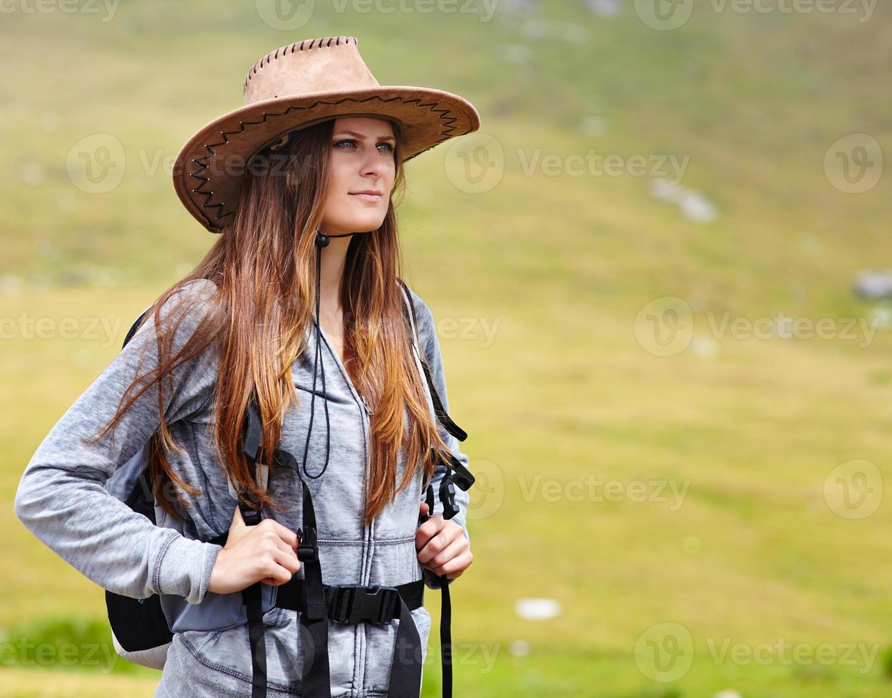 Female hiker with backpack and hat photo