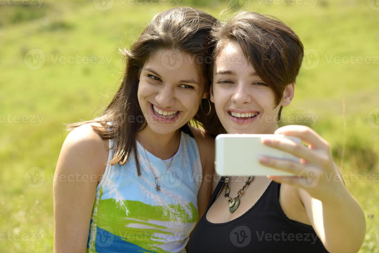 twee mooie jonge vrouwen die buiten foto's met telefoon nemen foto