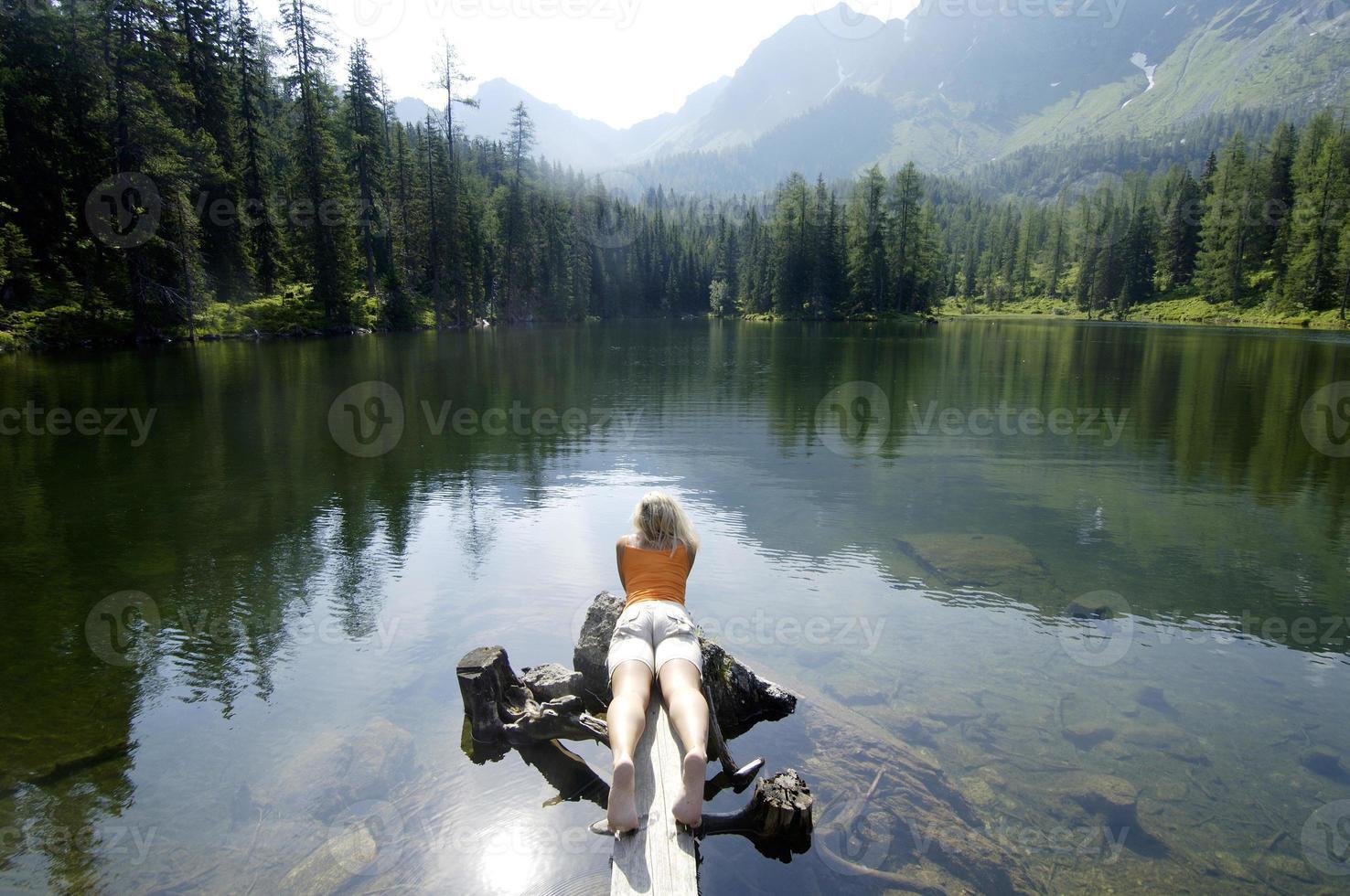 jonge vrouw liggend op een houten plank aan het meer foto