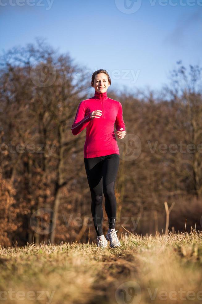 Young woman running outdoors in a city park photo