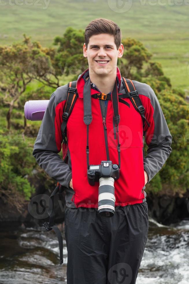 homem bonito em caminhada com a câmera no pescoço foto