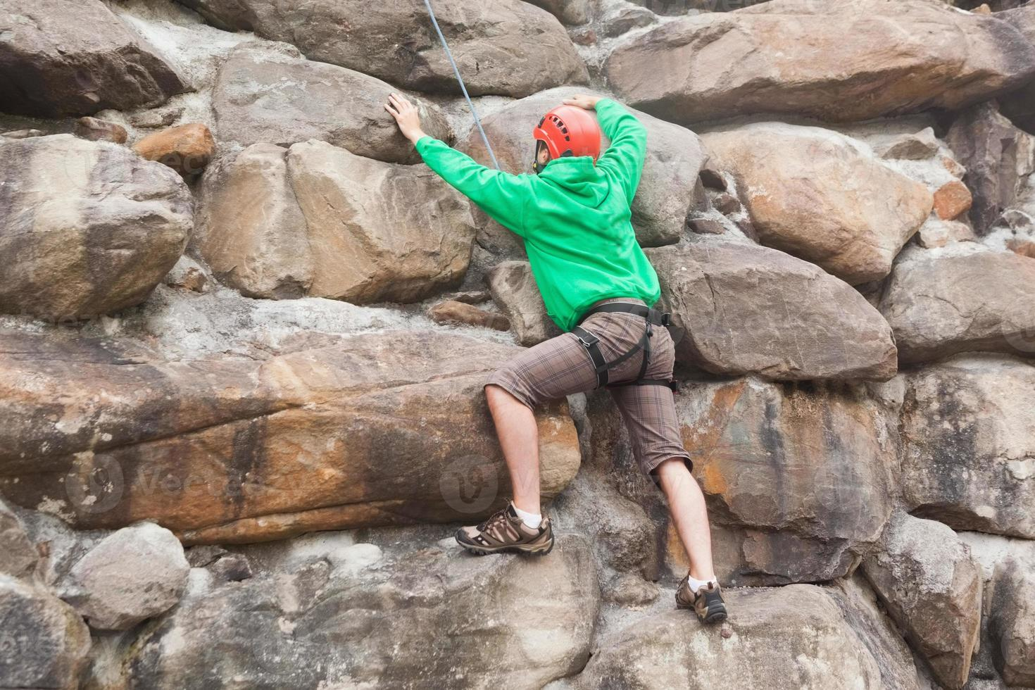 Determined man scaling a huge rock face photo