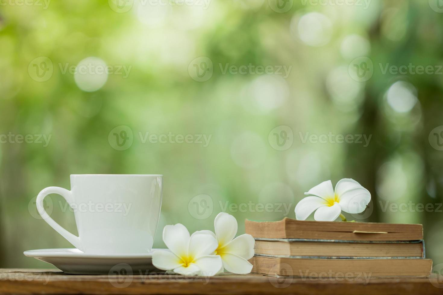 Livre de tasse de café et fleur de frangipanier blanc sur table photo