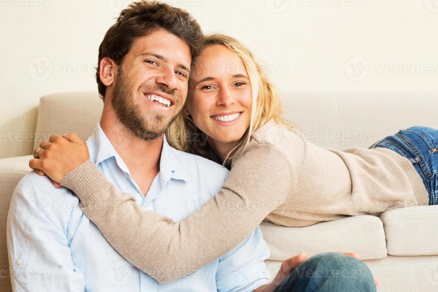 jovem casal feliz em casa no sofá foto