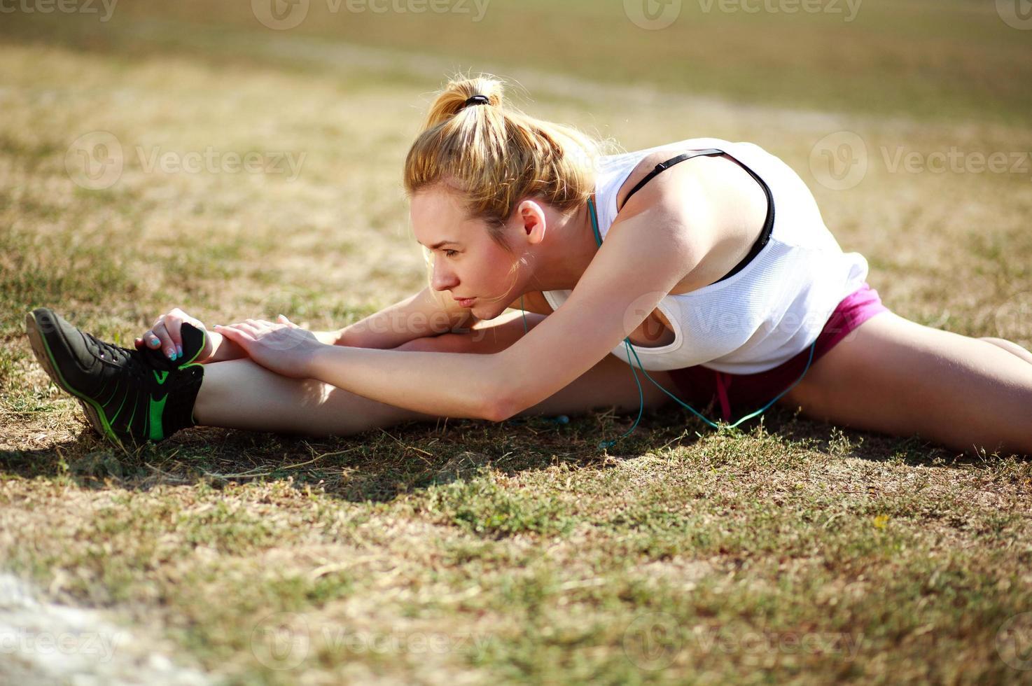 jovem fazendo exercícios de alongamento, treino na grama foto