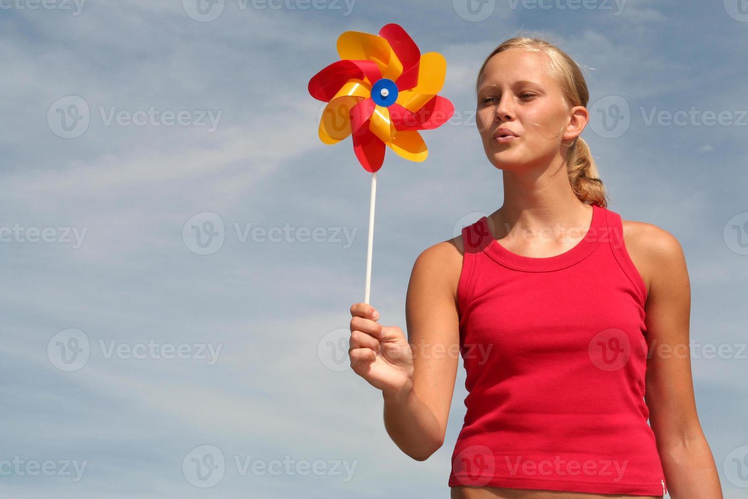 jonge vrouw waait pinwheel foto