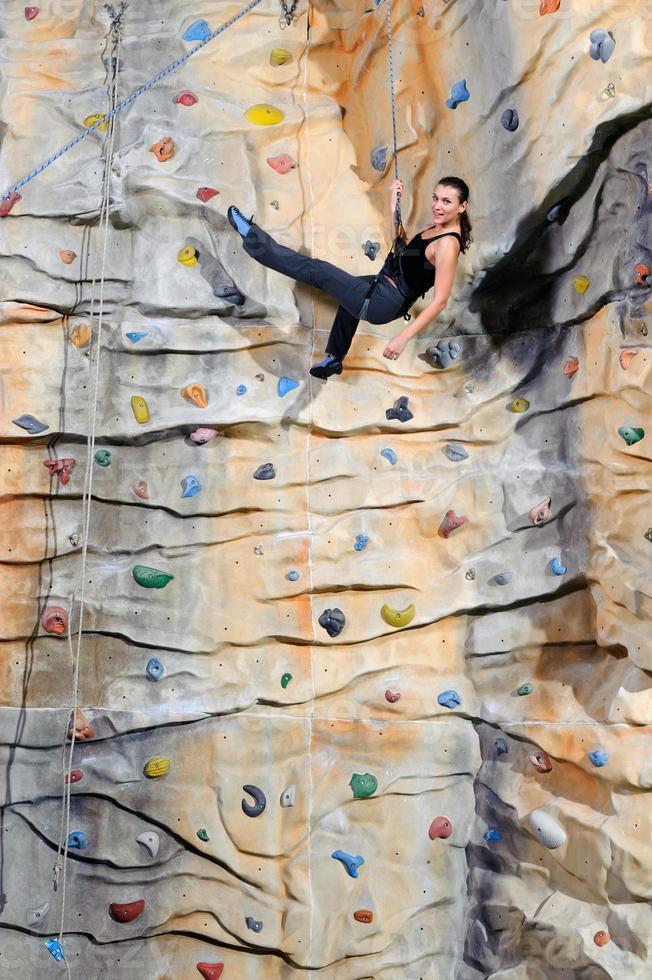 Mujer sobre pared de roca en el centro deportivo foto