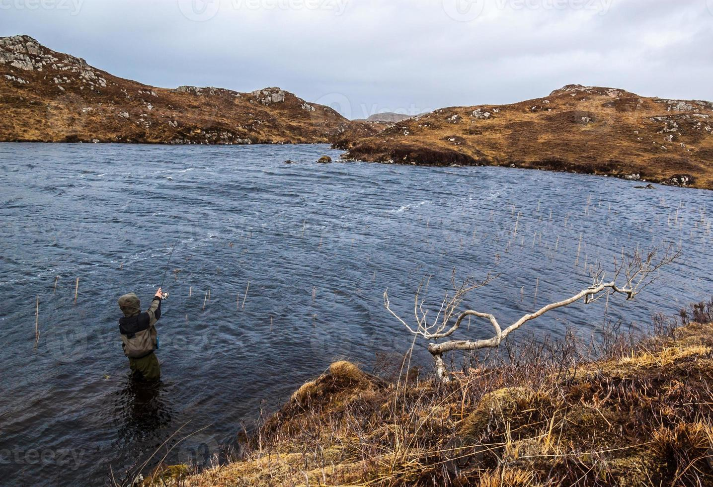 Man fishing for trout and salmon in a Scottish loch photo