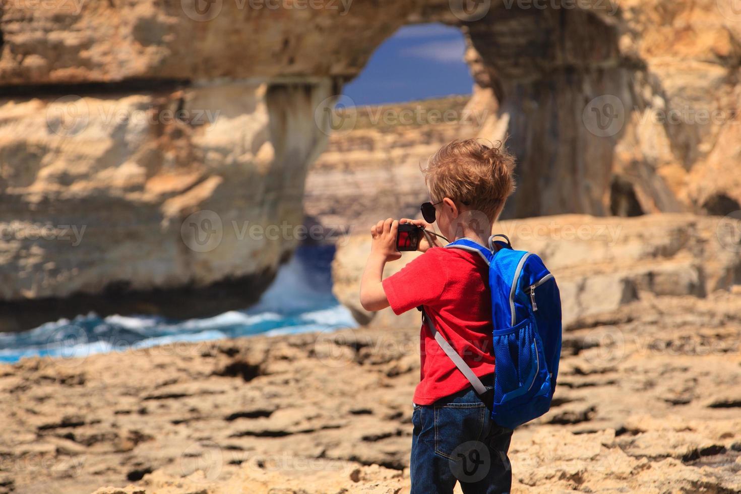 kleine jongen die foto van azuurblauw venster op gozo-eiland maakt