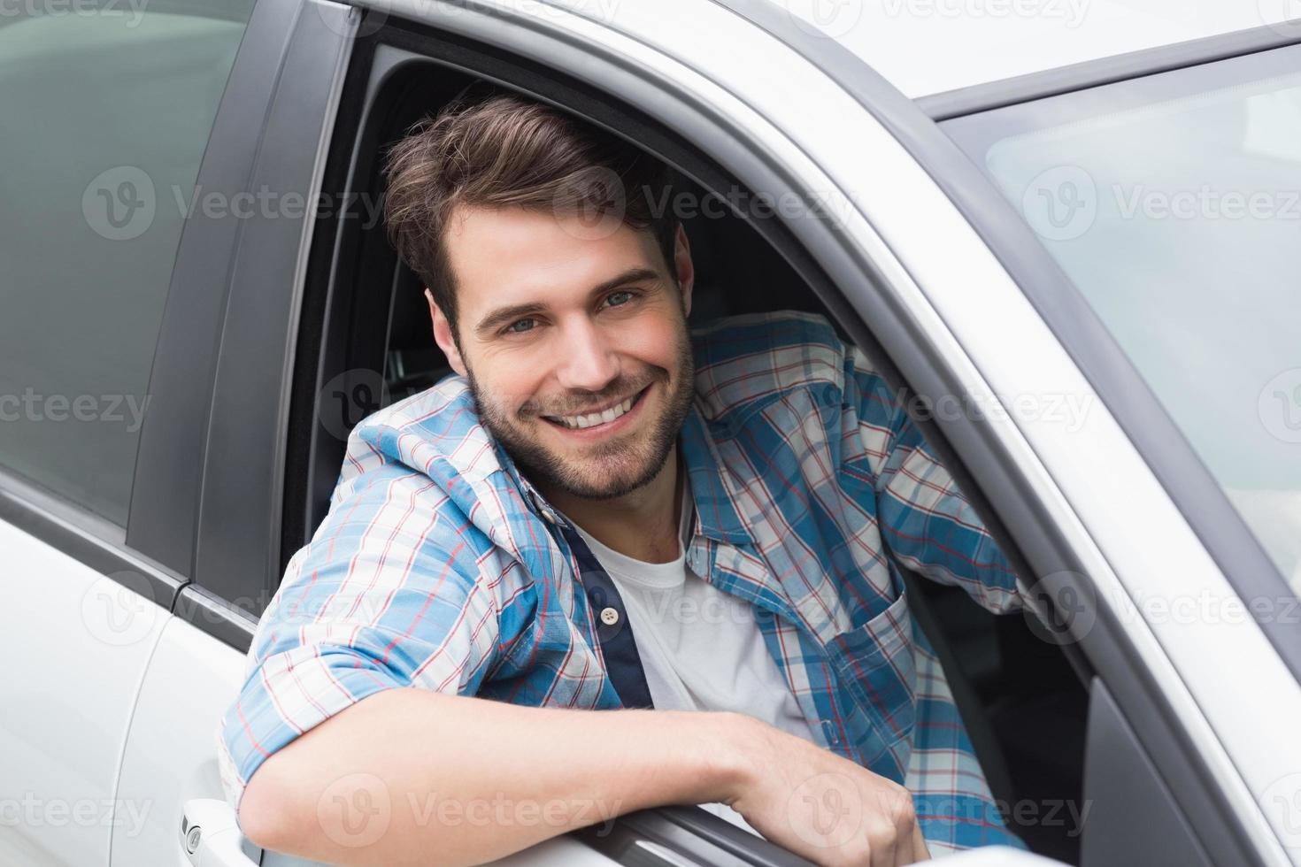 Young man driving and smiling photo