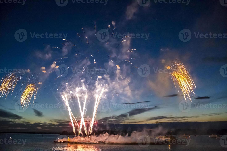 Coloridos fuegos artificiales en el fondo del cielo sobre el agua foto