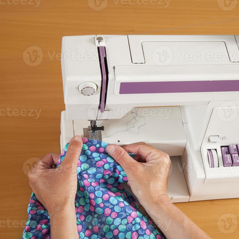 coser con máquina de alcantarillado, manos y tela foto