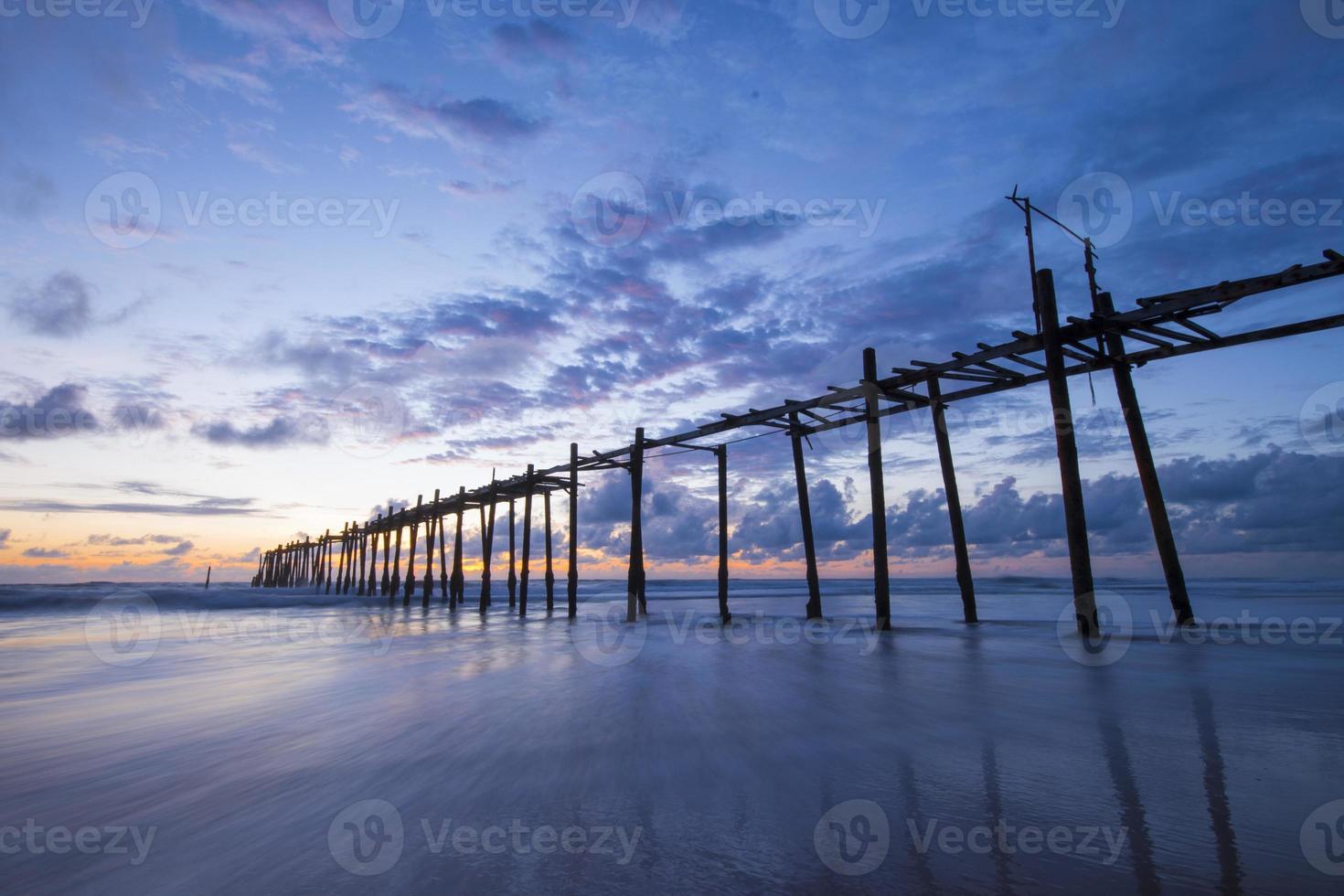 Viejo puente de madera en la playa de Natai con hermoso cielo foto