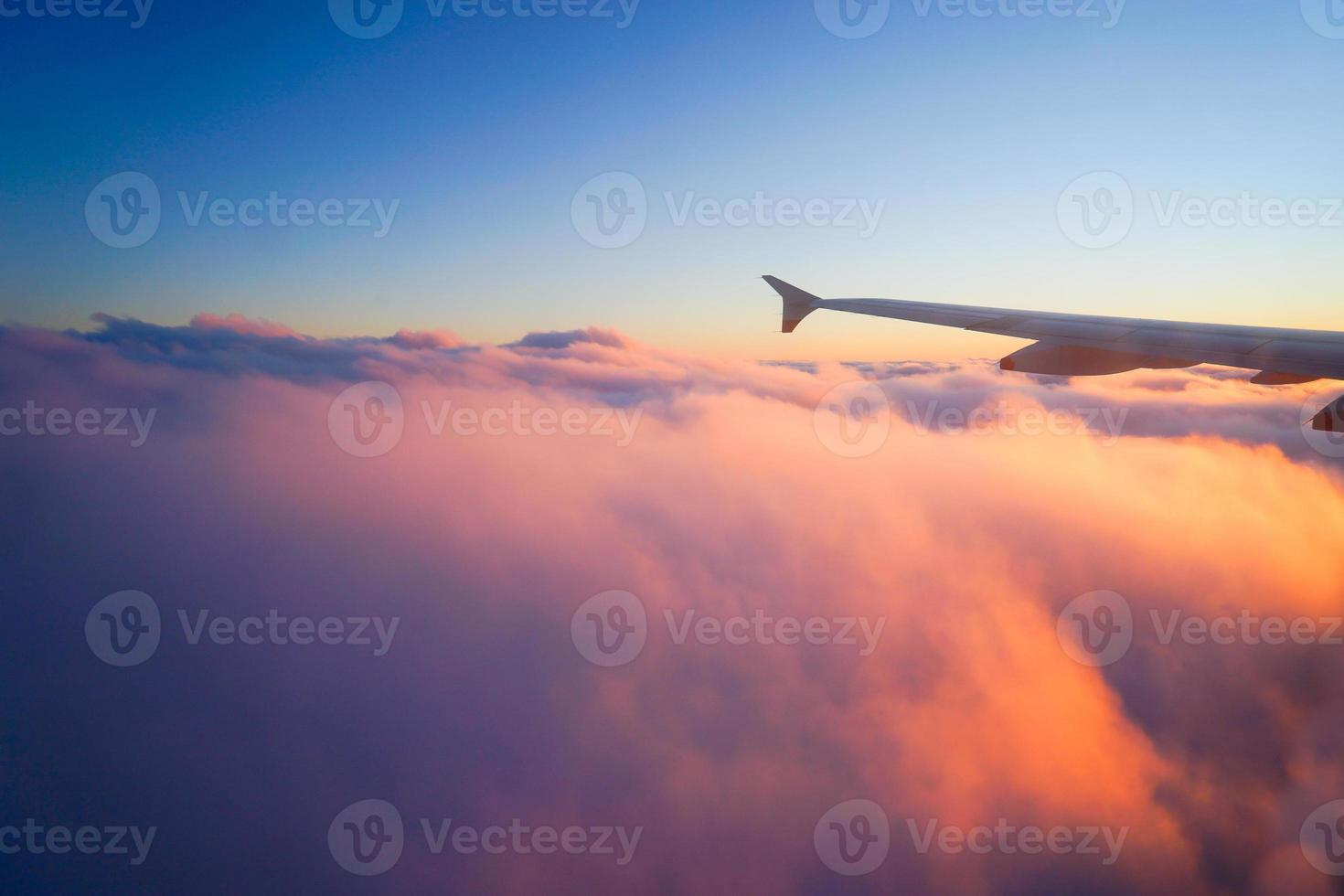 Airplane Wing in Flight from window, sunset sky photo