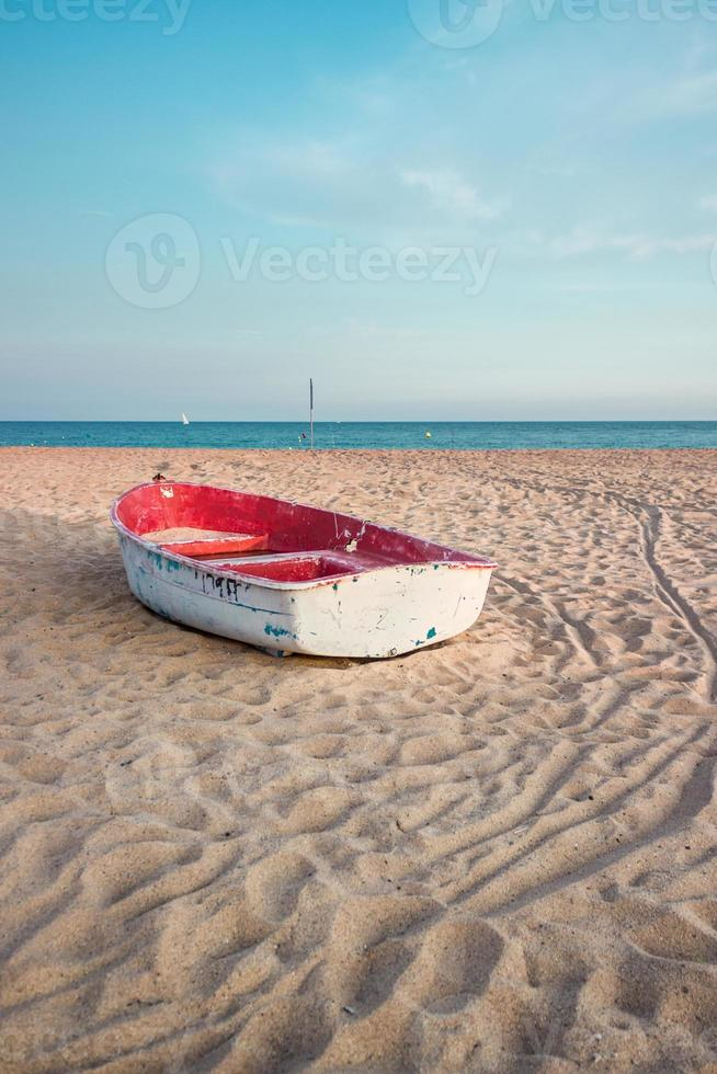 small fishing boat on the beach and blue sky photo