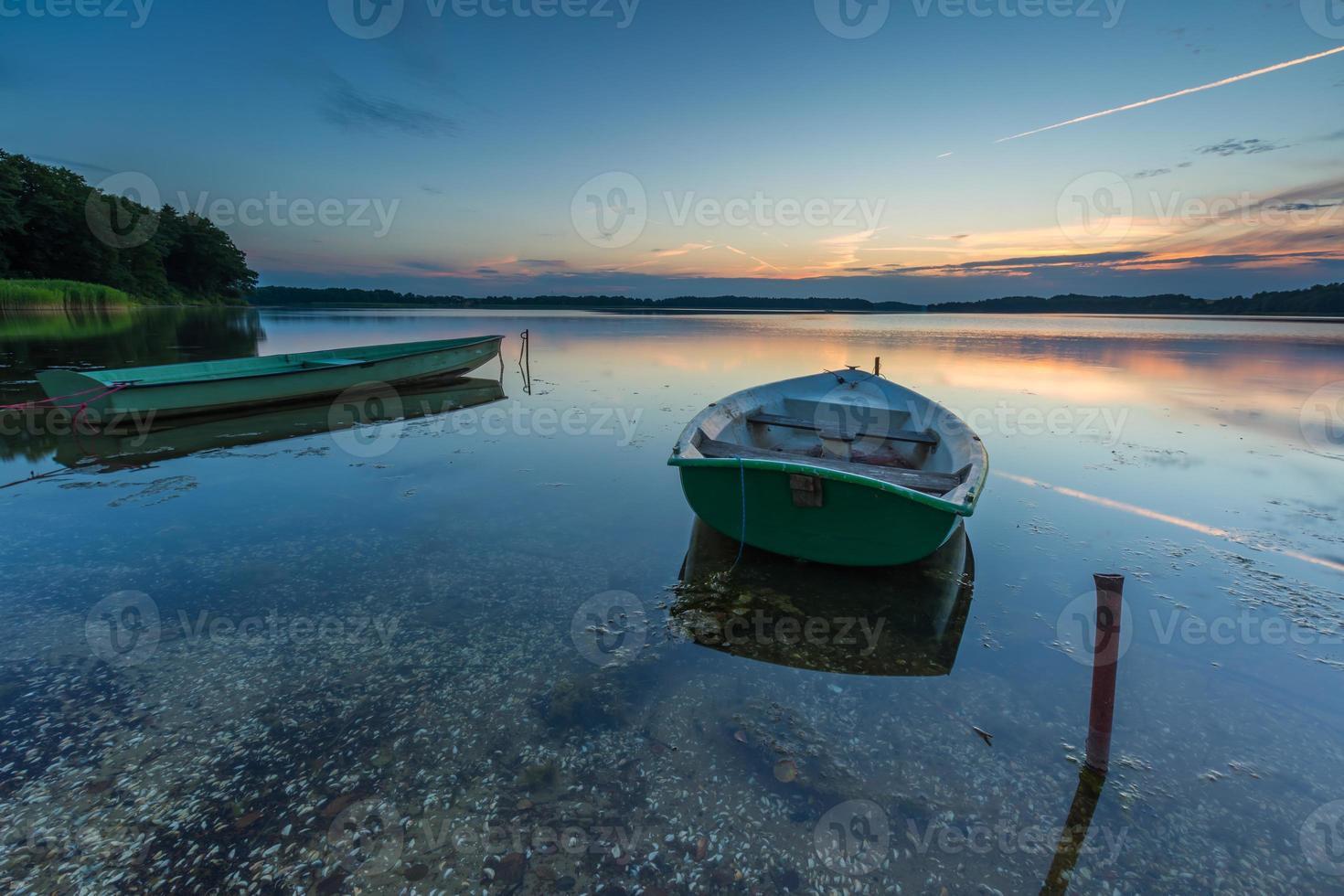 Fisherman boats moored on lake shore under sunset sky photo