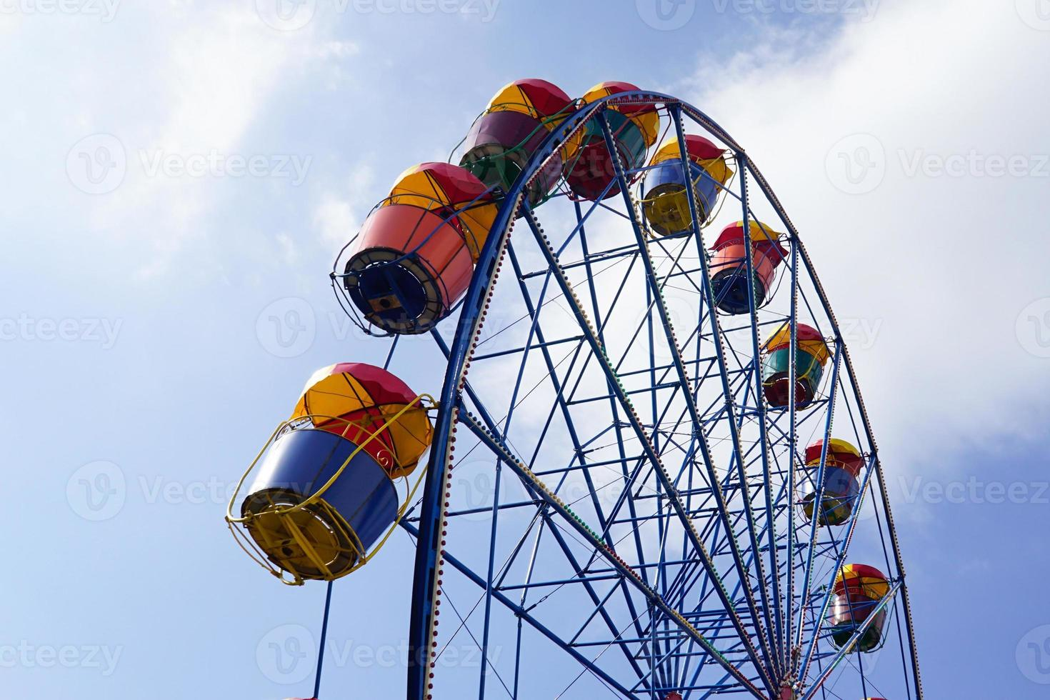 Colorful ferris wheel with cloudy blue sky at background photo