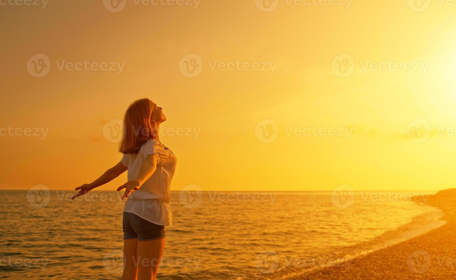 happy young woman open her arms to sky  at sunset photo