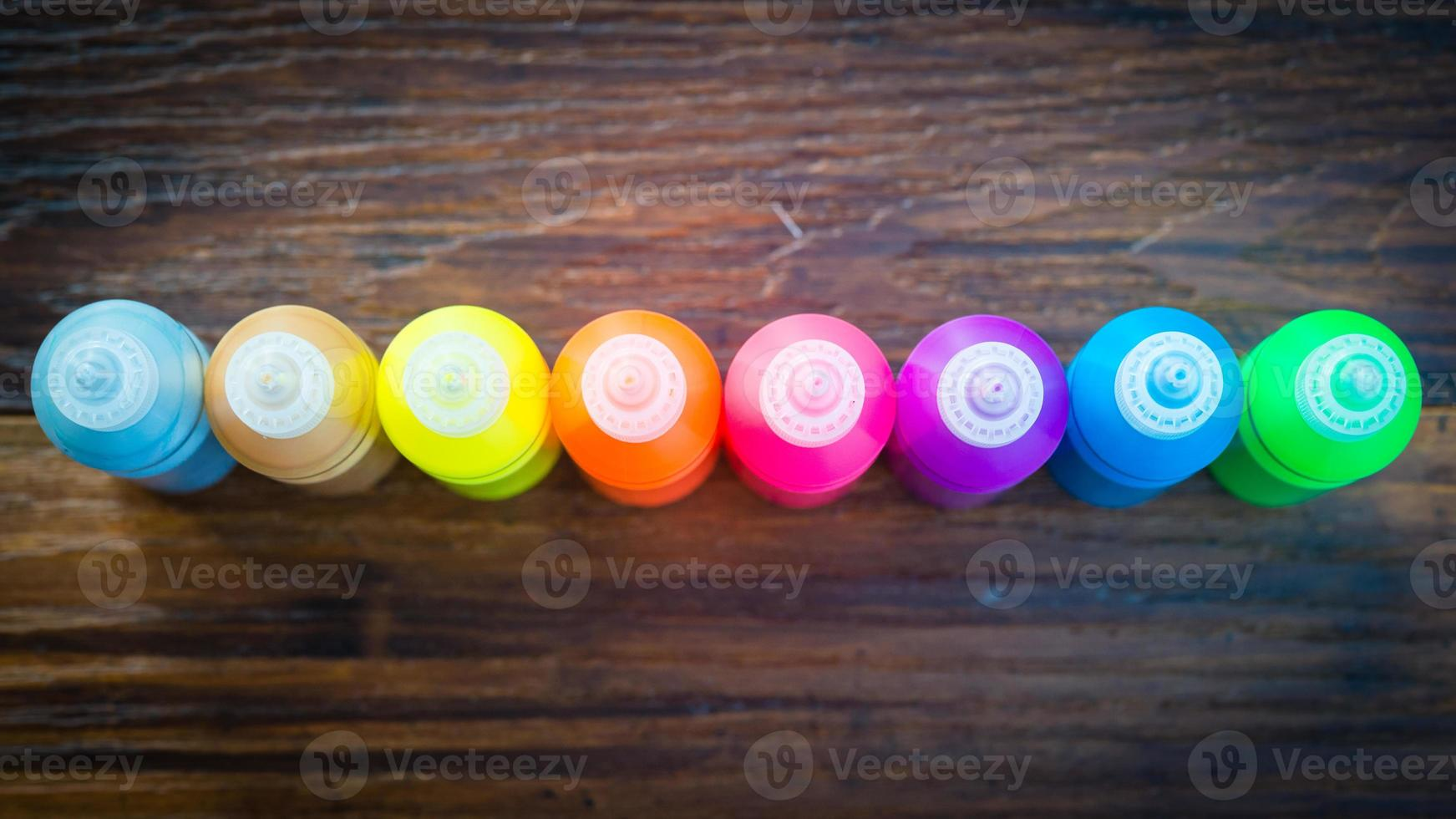 Colorful paint - bottles with colorful pigments on wooden background photo