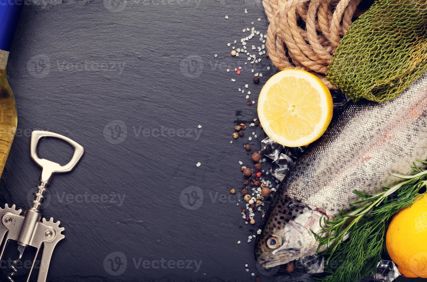 Fresh raw rainbow trout fish and white wine photo