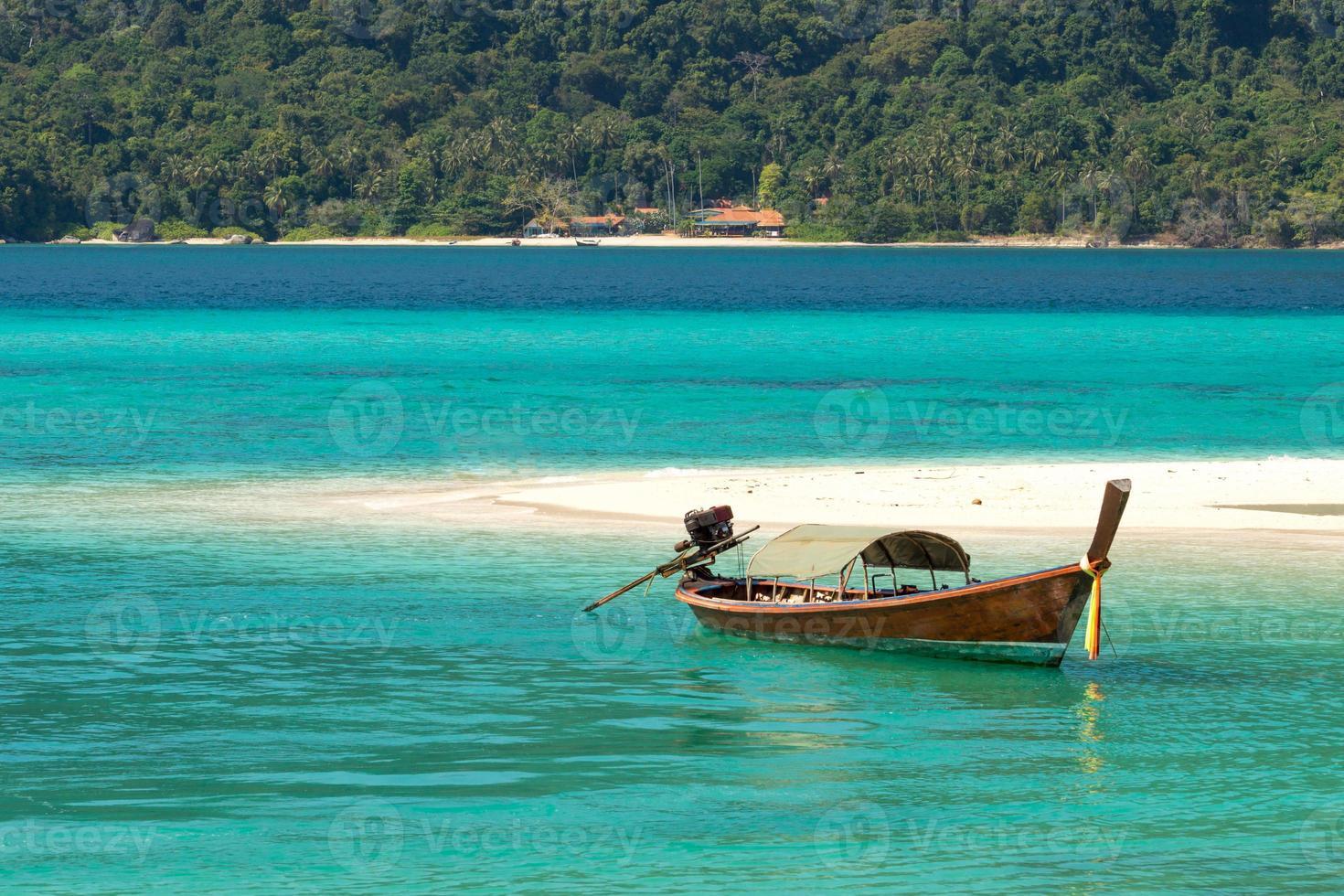 Barco de cola larga en aguas cristalinas de color turquesa y playa tropical foto