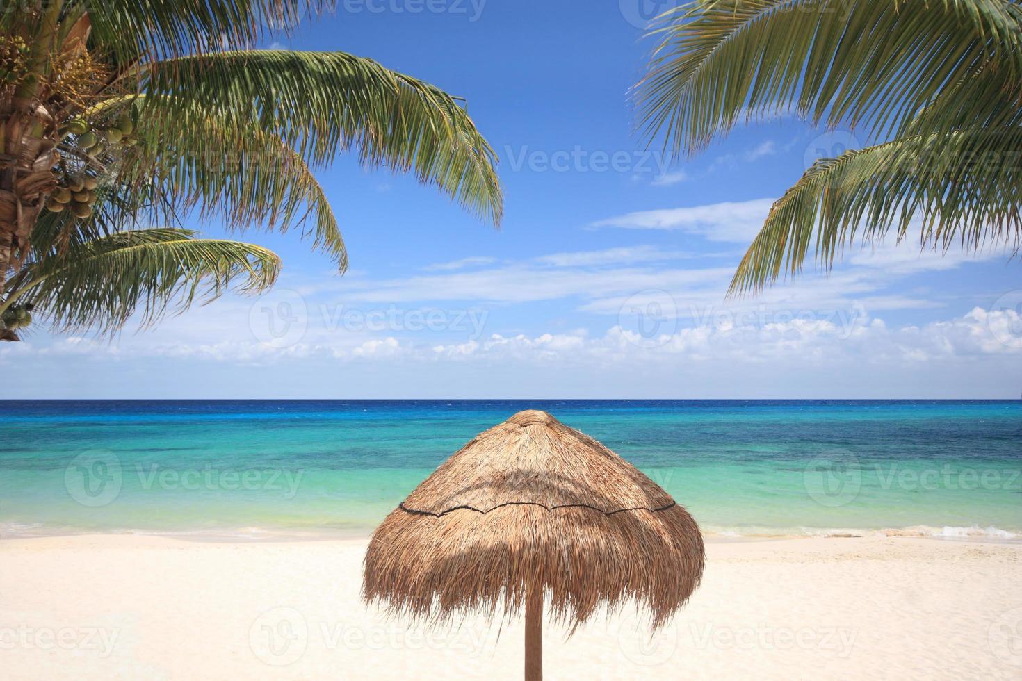 sombrilla de paja en la playa tropical foto
