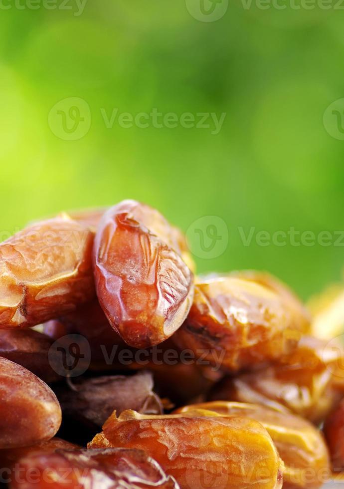 Fresh dates  on green background photo