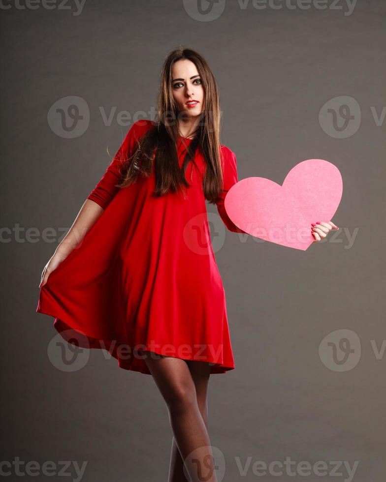 Woman in red dress holds heart sign photo