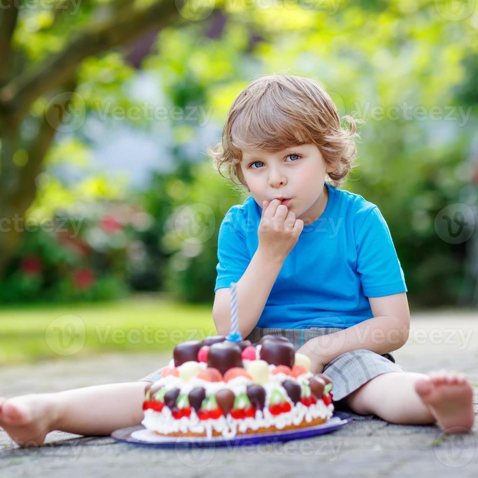 Little boy celebrating his birthday with big cake photo