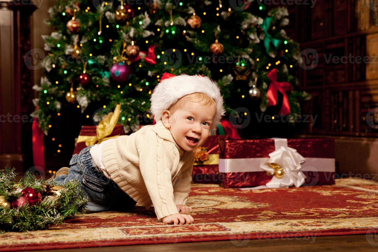 Baby near the Christmas tree. Little boy celebrating Christmas. photo