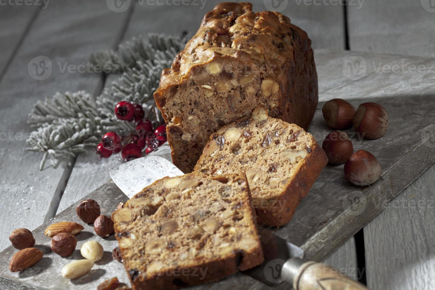 Christmas fruitcake with nuts and christmas decorations on wooden board photo