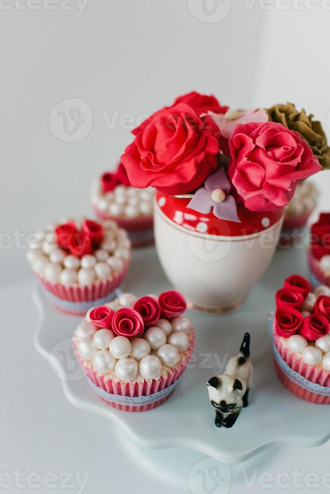 Close-up of party cupcakes and sugared roses photo