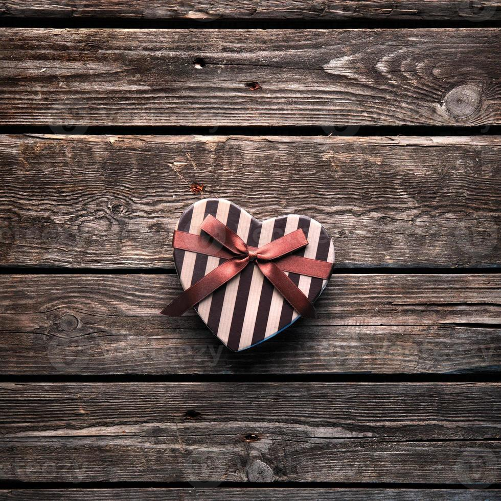Heart-shaped Valentines Day gift box on wooden table. photo