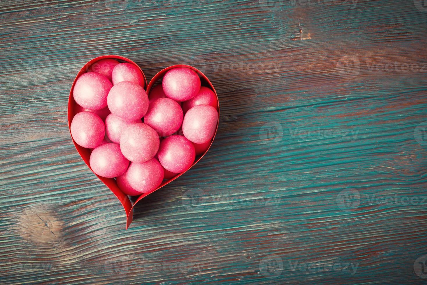 Sweet candies in heart shaped boxes on vintage wooden background photo