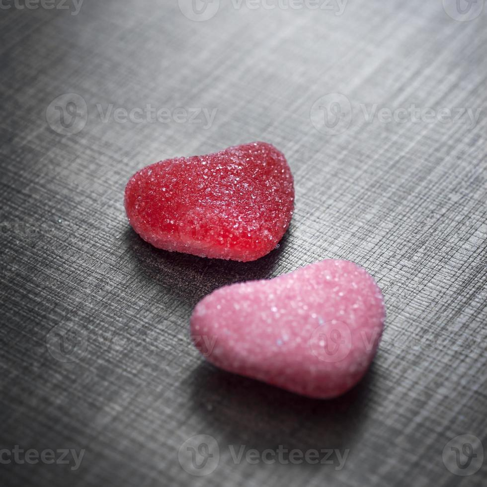 Candy in shape of hearts on wooden background photo