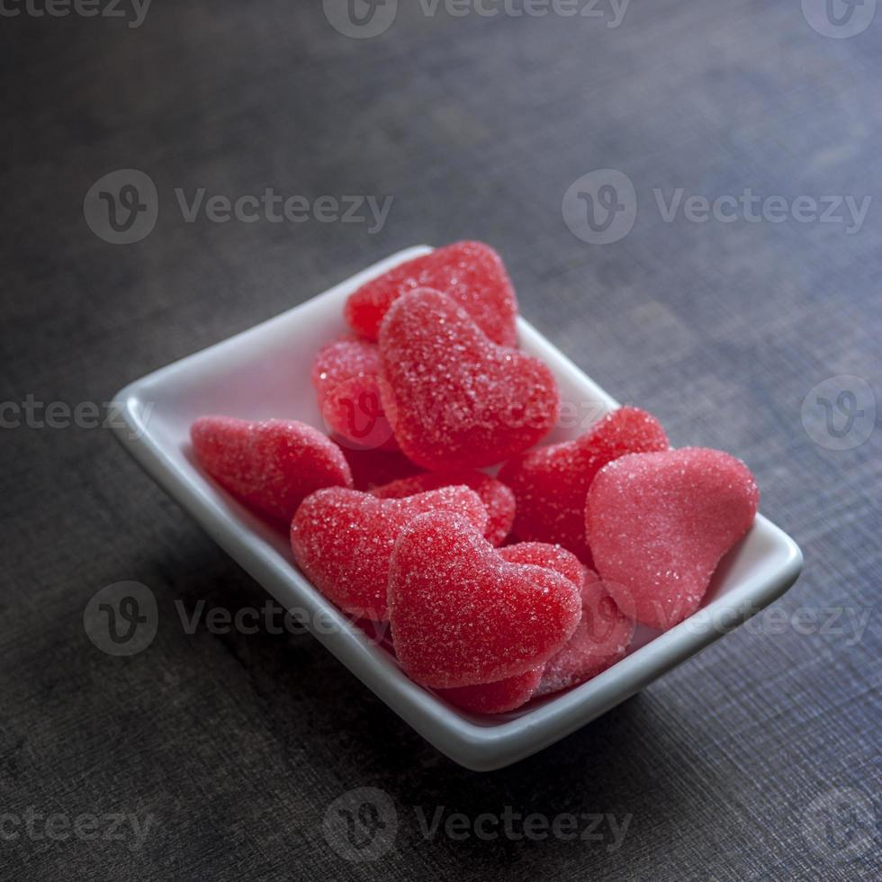 Candy in shape of hearts on wooden background. photo
