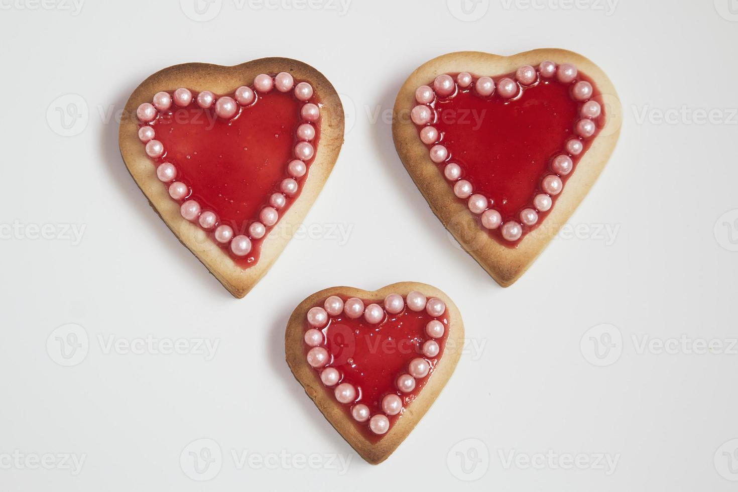 Three romantic heart shaped homemade Valentine cookies over a wh photo