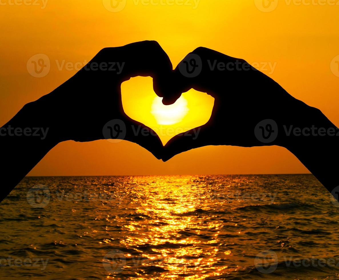 Silhouette hand in heart shape and sunrise over the ocean photo