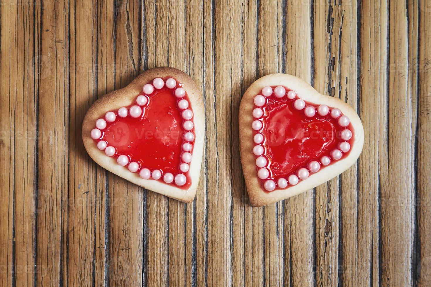 Two red hearts cookies on wooden background photo