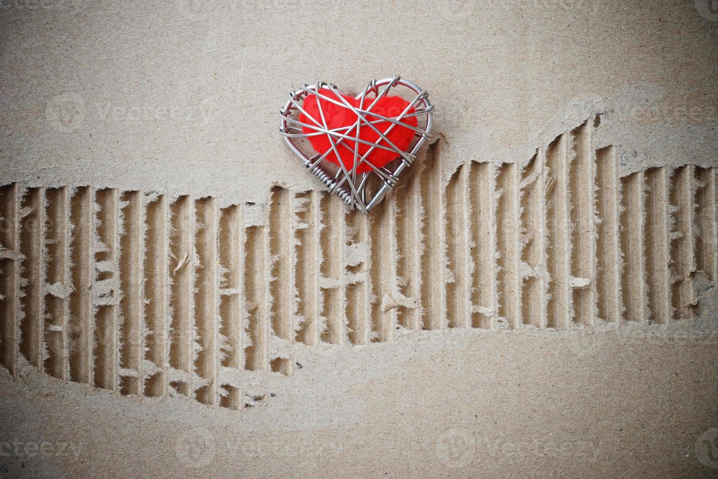 red heart on torn grunge cardboard paper photo