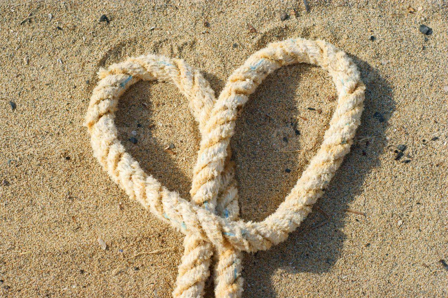 rope with a heart knot  - sand background photo
