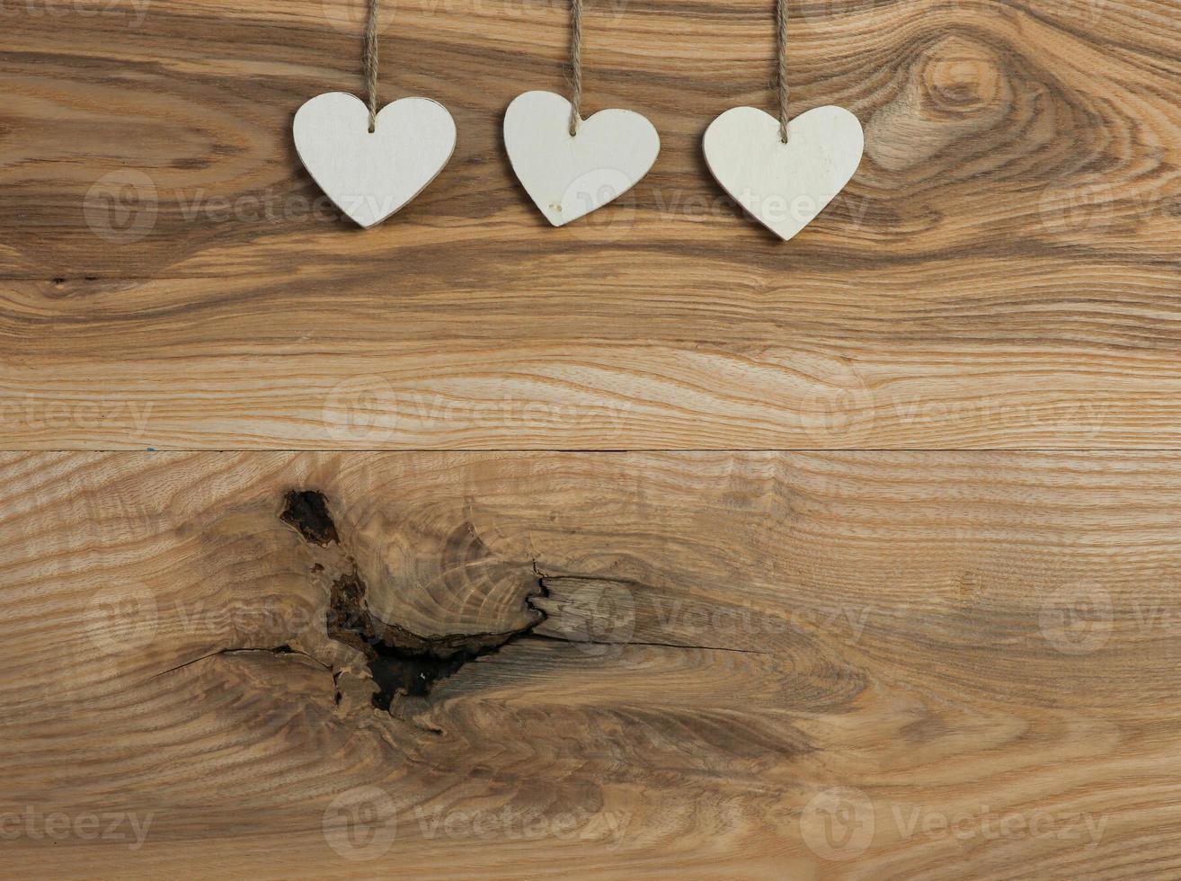 três corações brancos do amor dos namorados pendurados em uma textura de madeira foto