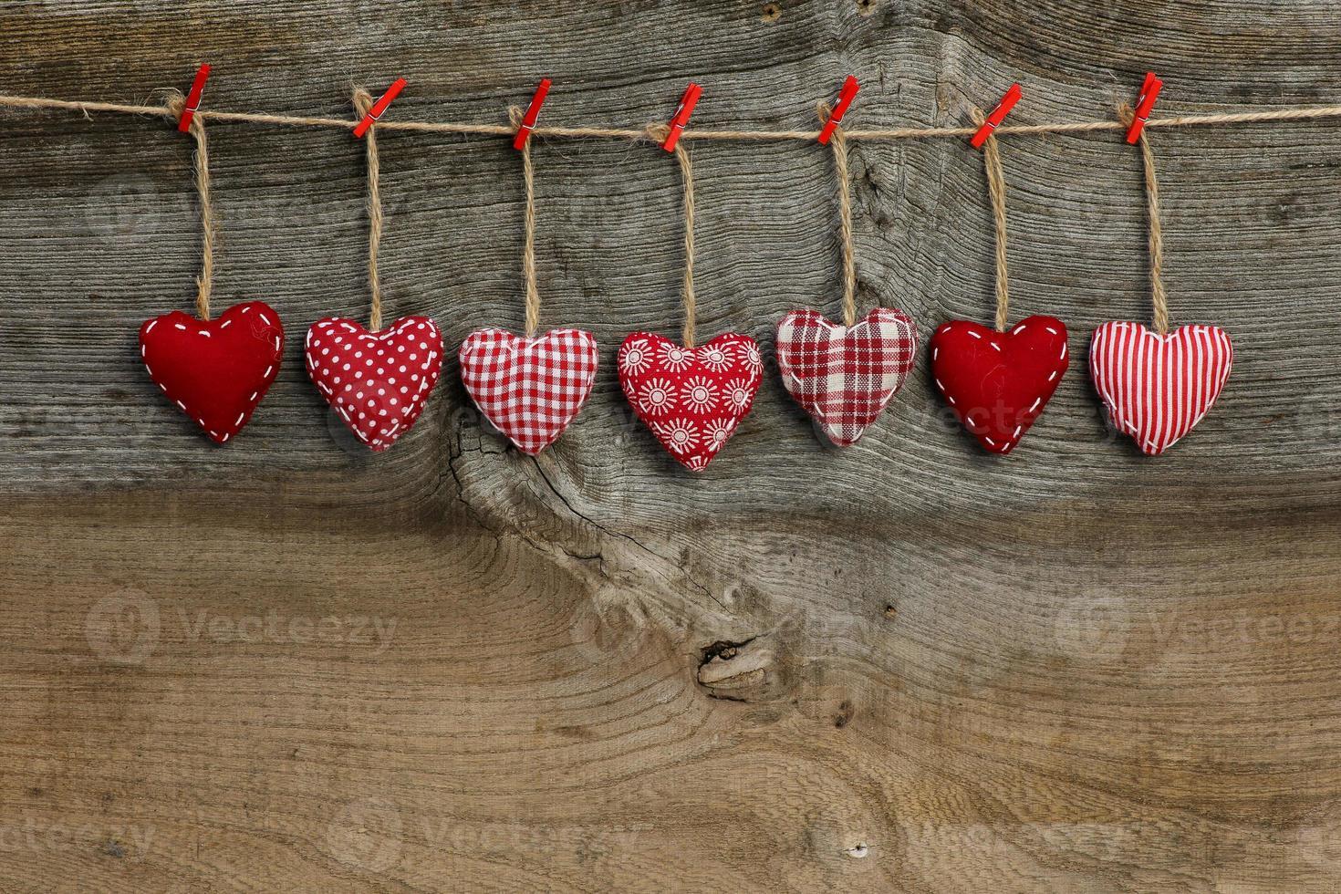 corações de dia dos namorados amor guingão pendurados em uma textura de madeira foto