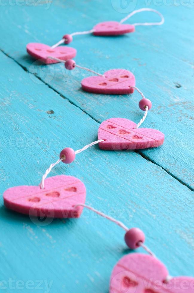 Pink decorative hearts on blue shabby background photo