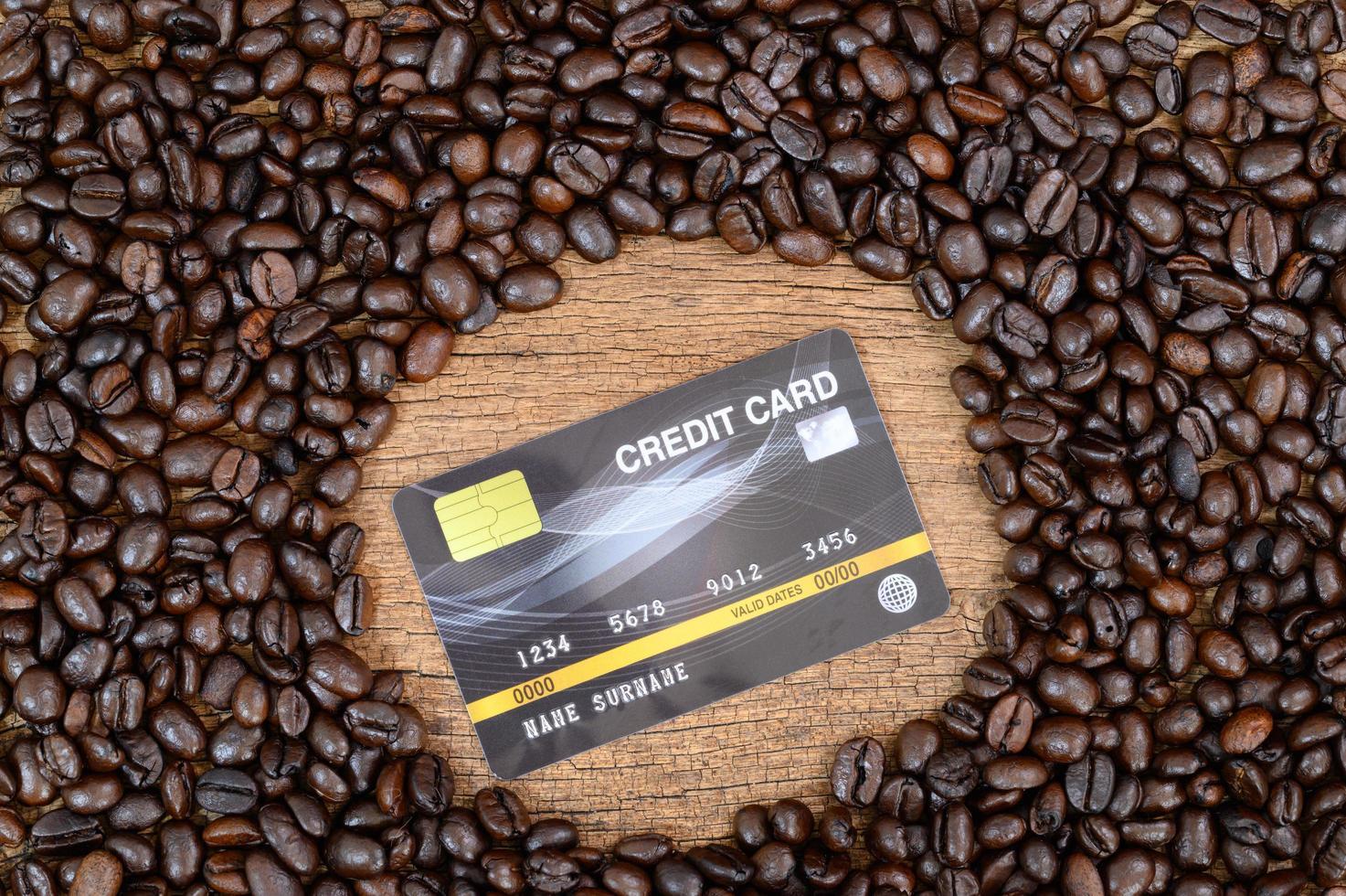 Kreditkarte und Kaffeebohnen auf dem Schreibtisch foto