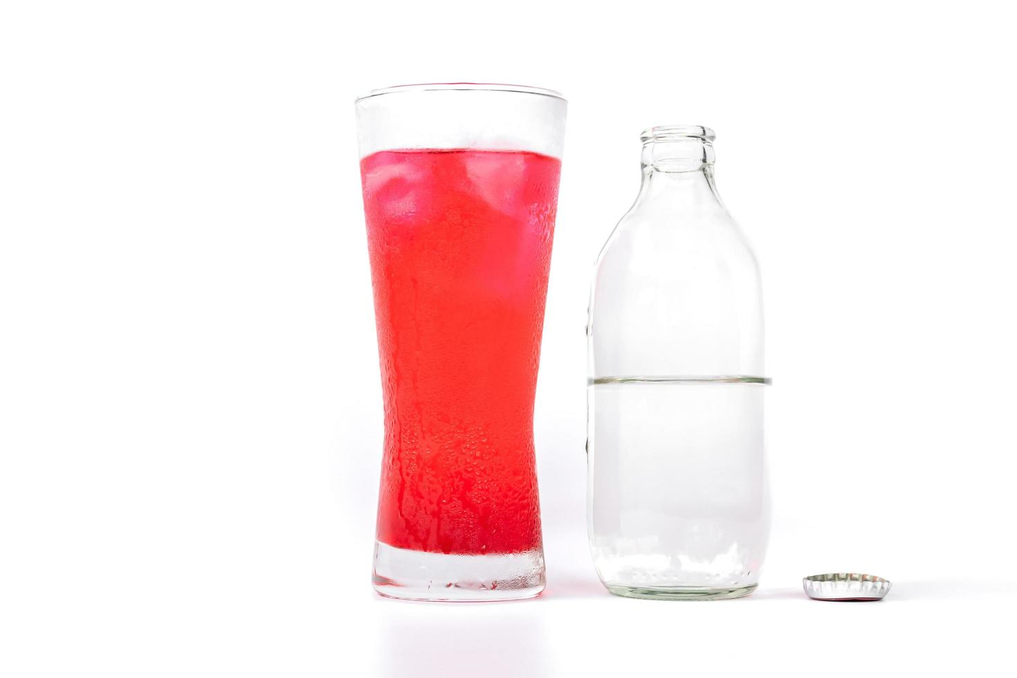 vaso de néctar rojo mezclado con refresco y botella de refresco foto
