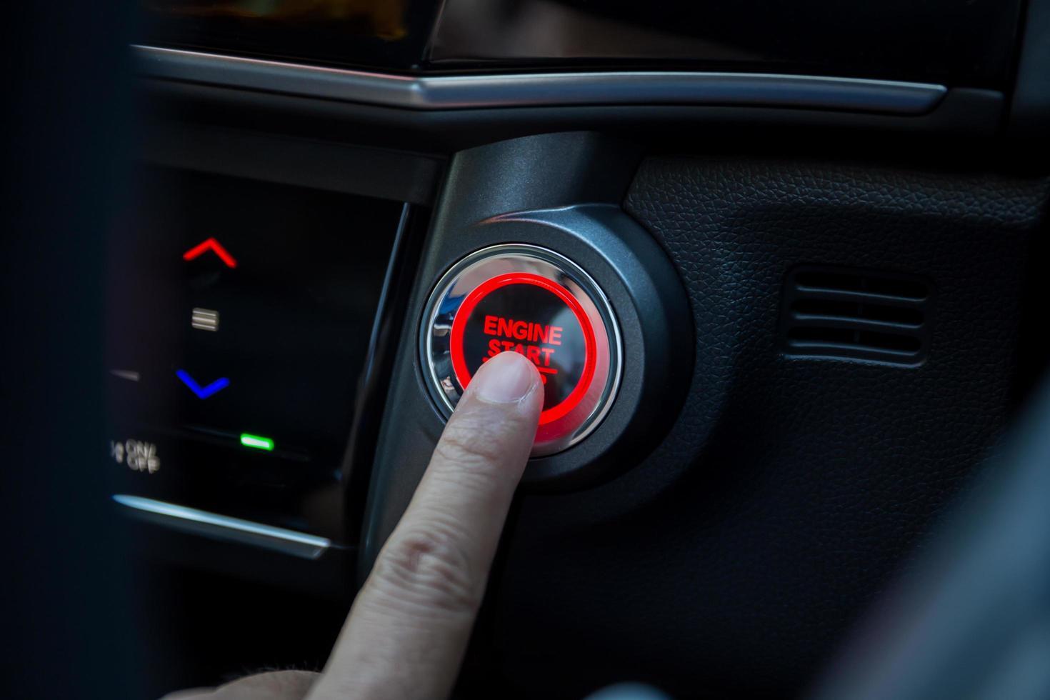 doigts appuyant sur le bouton de démarrage de la voiture photo