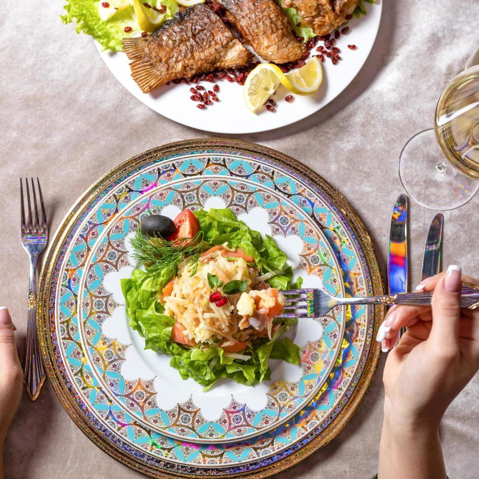 donna che mangia un'insalata di pesce foto