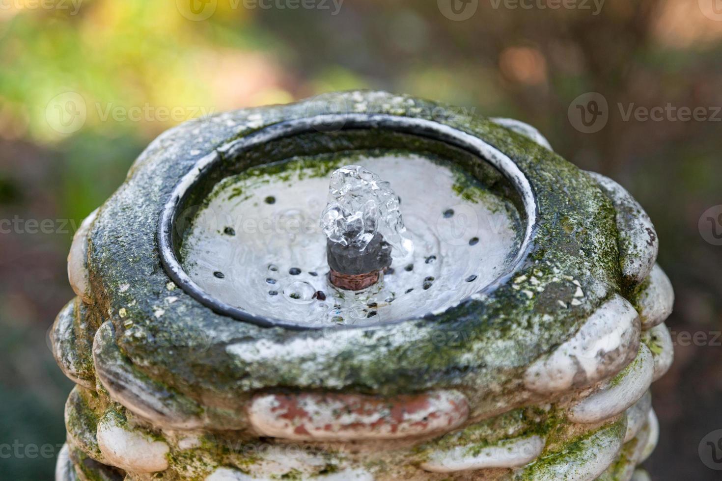 nascente de água artificial e torneira de metal foto